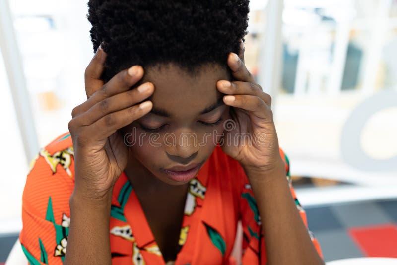Designer gráfico fêmea forçado que senta-se na mesa imagem de stock
