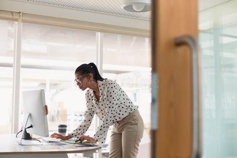 Designer gráfico fêmea que come o café ao usar a tabuleta gráfica na mesa fotografia de stock