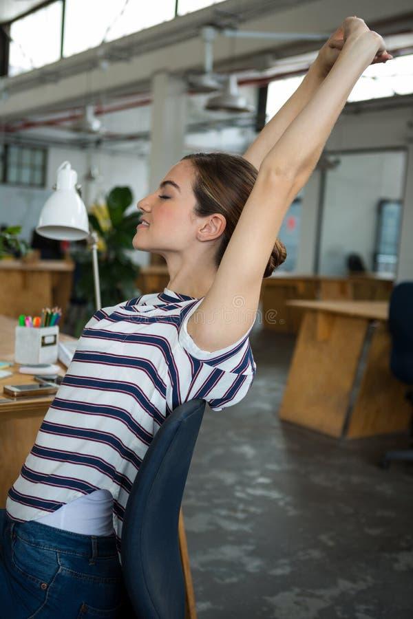 Designer gráfico fêmea que senta-se na cadeira e que estica seus braços fotografia de stock royalty free