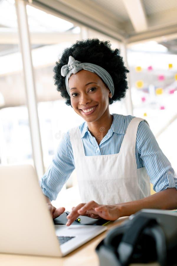 Designer gráfico fêmea que trabalha no portátil na mesa imagens de stock