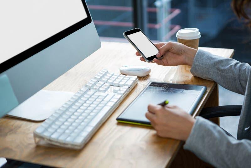 Designer gráfico fêmea que usa a tabuleta e o telefone celular de gráficos na mesa imagem de stock