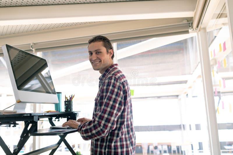 Designer gráfico masculino que trabalha no computador na mesa no escritório imagem de stock royalty free
