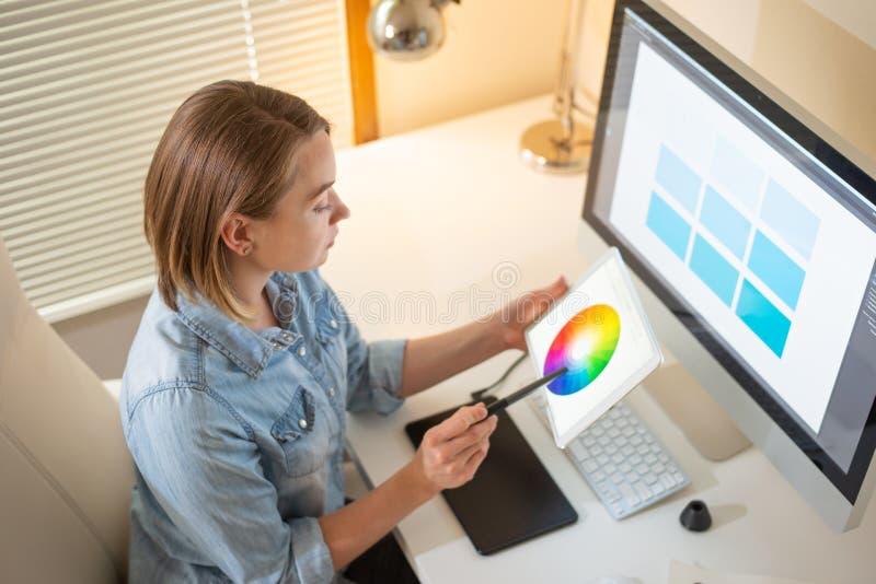 Designer gráfico que senta-se no trabalho illustrator Desenhista da Web freelancer imagem de stock