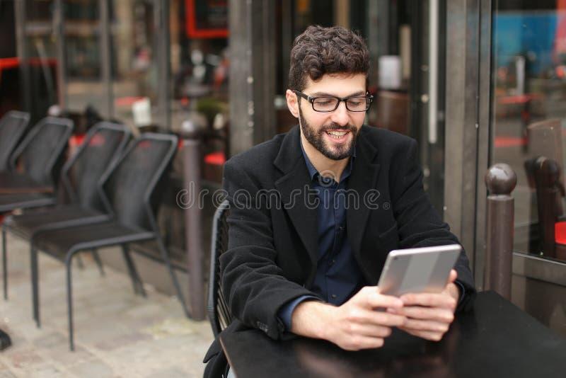 Designer gráfico que trabalha com tabuleta e papéis na tabela do café dentro fotografia de stock