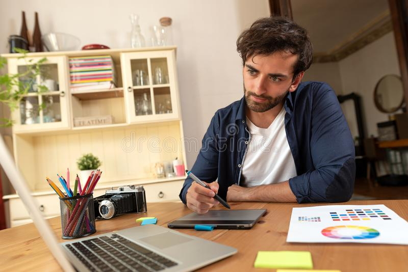 Designer gráfico que trabalha na tabuleta digital imagens de stock