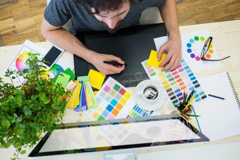 Designer gráfico que trabalha na tabuleta gráfica em sua mesa fotografia de stock