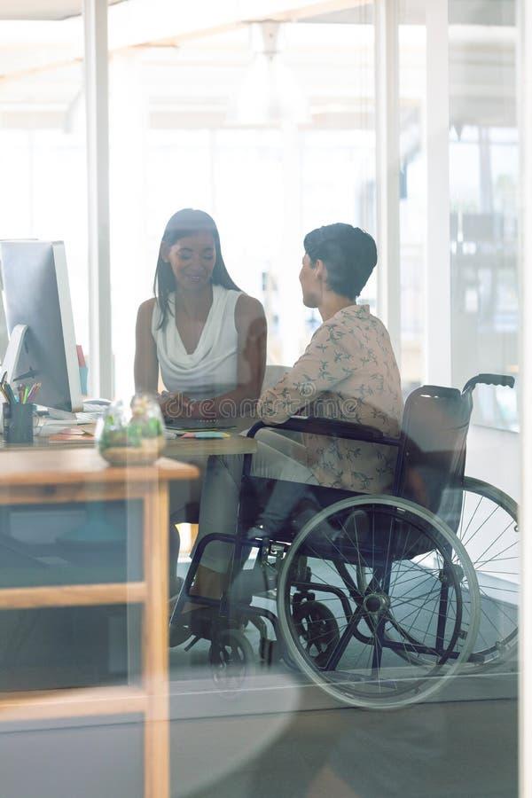 Designer gráficos fêmeas que interagem um com o otro na mesa em um escritório moderno imagem de stock