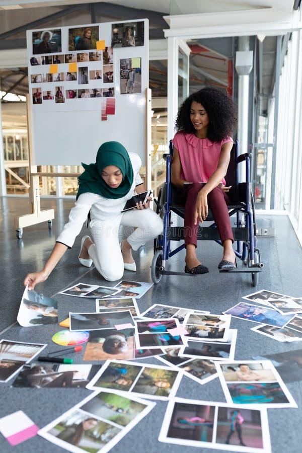 Designer gráficos fêmeas que olham fotografias no escritório fotos de stock royalty free