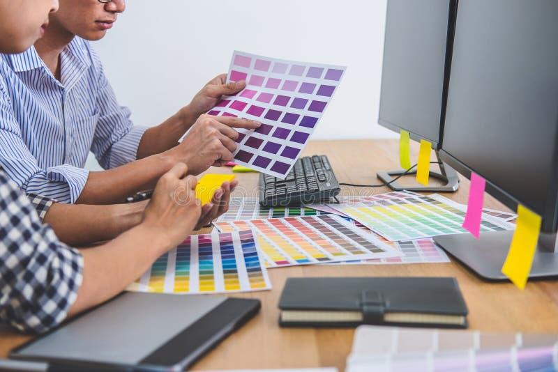 Designer gr?fico criativo de dois colegas que trabalha na sele??o de cor e que tira na tabuleta de gr?ficos no local de trabalho, fotografia de stock