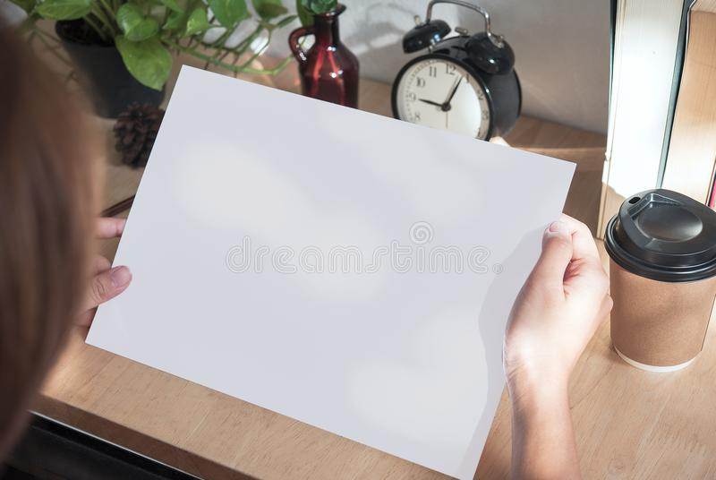 Designer hand showing blank paper A4 flyer for mockup template design logo branding on wooden background. Hand showing blank paper A4 flyer for mockup template royalty free stock photo