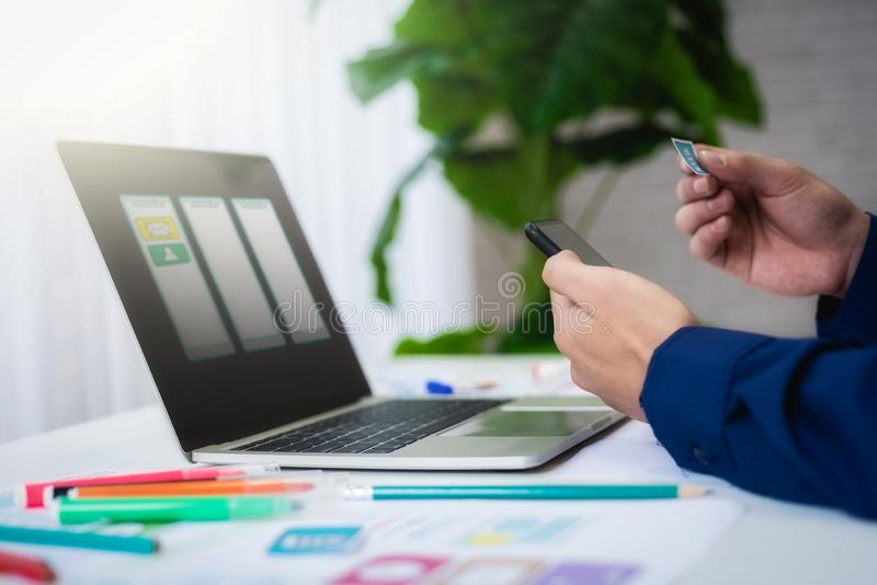 Designer man mobile application test new app features. He working with computer and mobile phone. User experience Design concept royalty free stock photos