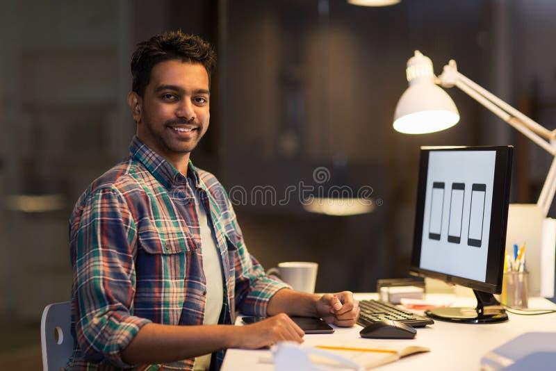 Designer mit dem Computer, der im Nachtbüro arbeitet stockbilder