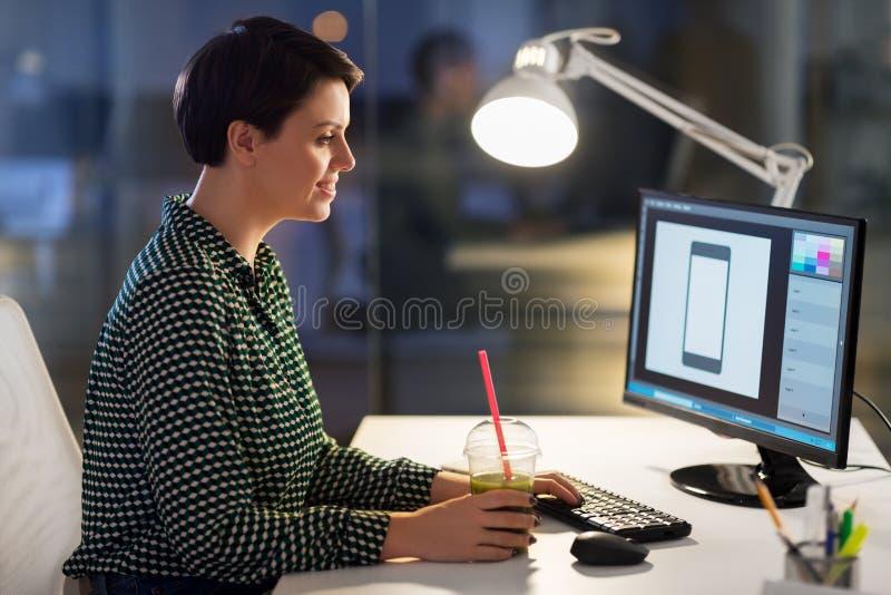 Designer mit Smoothie am Computer im Nachtb?ro lizenzfreies stockfoto