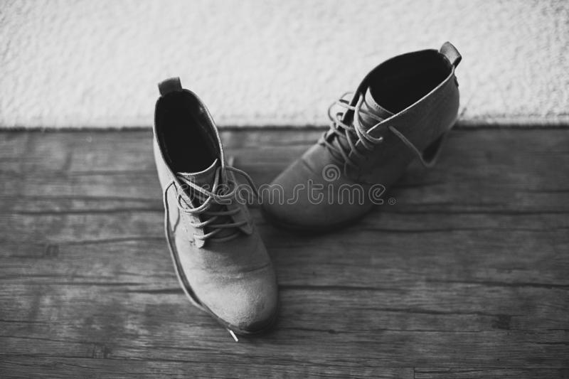 Designer modern, worn, used, suede, women`s shoes with a low heel, with untied laces, against a wooden floor and carpet. Black an royalty free stock photography