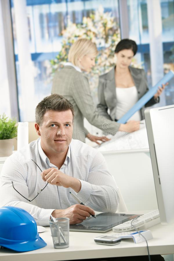 Designer In Office With Coworkers Royalty Free Stock Image