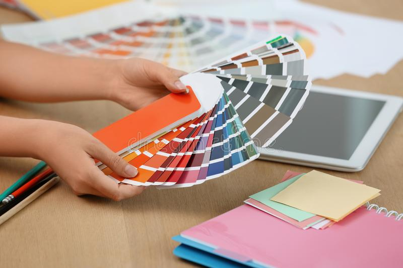 Designer with paint color palette samples at table stock images