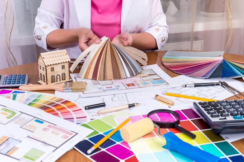 Designer`s hands showing colourful sampler at workplace.  royalty free stock photography