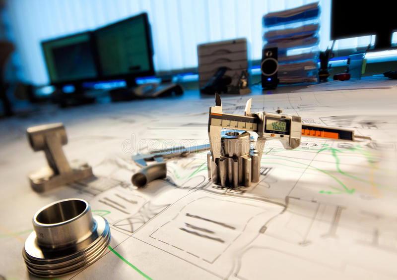 On the designer`s table. Industrial designer table with calipers and fittings stock photo