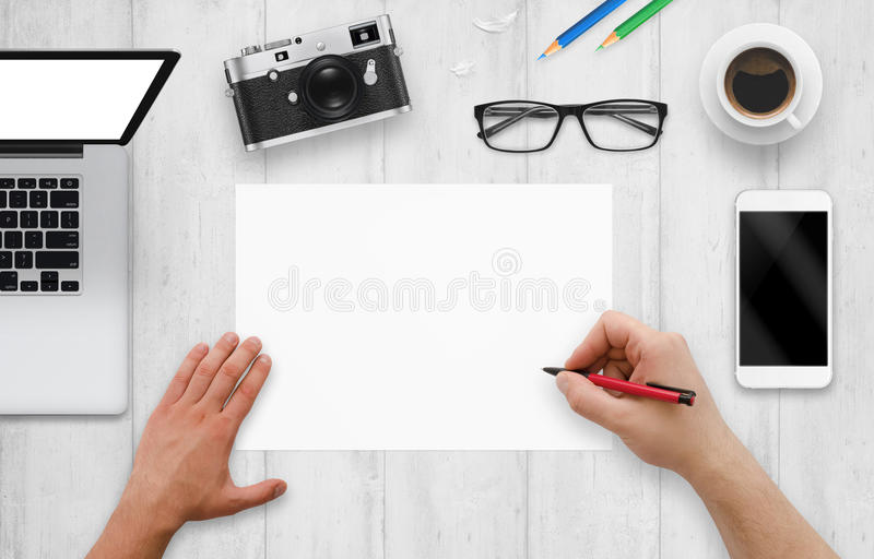 Designer schreibt auf ein leeres Papier Draufsicht des Arbeitsschreibtisches mit Computer, Telefon, Kamera, Gläser, Kaffee lizenzfreie stockfotografie