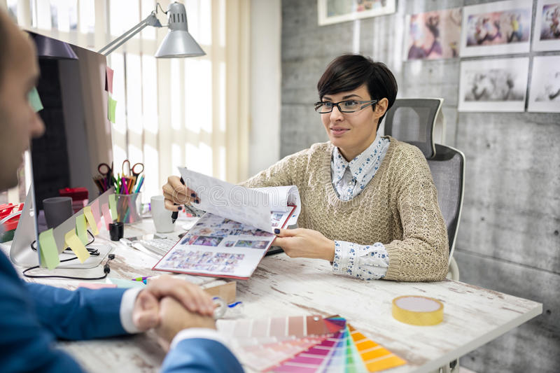 Designer showing palette color to client. In her studio stock photography