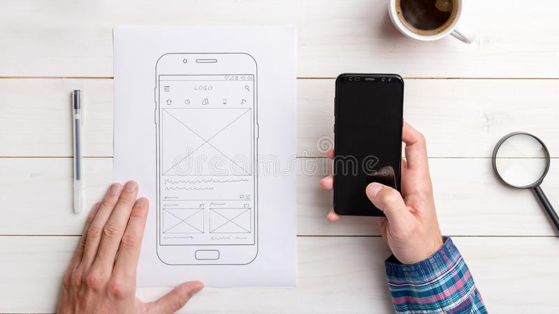 Designer tests the user interface and user experience on a mobile phone. Wireframe beside with mobile phone with a sketched app. The concept of designing stock photo
