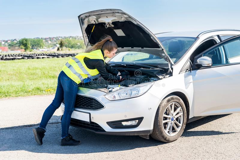 Woman testing car battery in broken car on roadside royalty free stock images