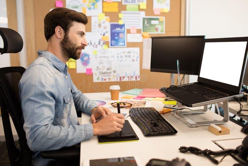 Designer using digitizer and stylus on creative office desk. Side view of designer using digitizer and stylus on creative office desk stock photo