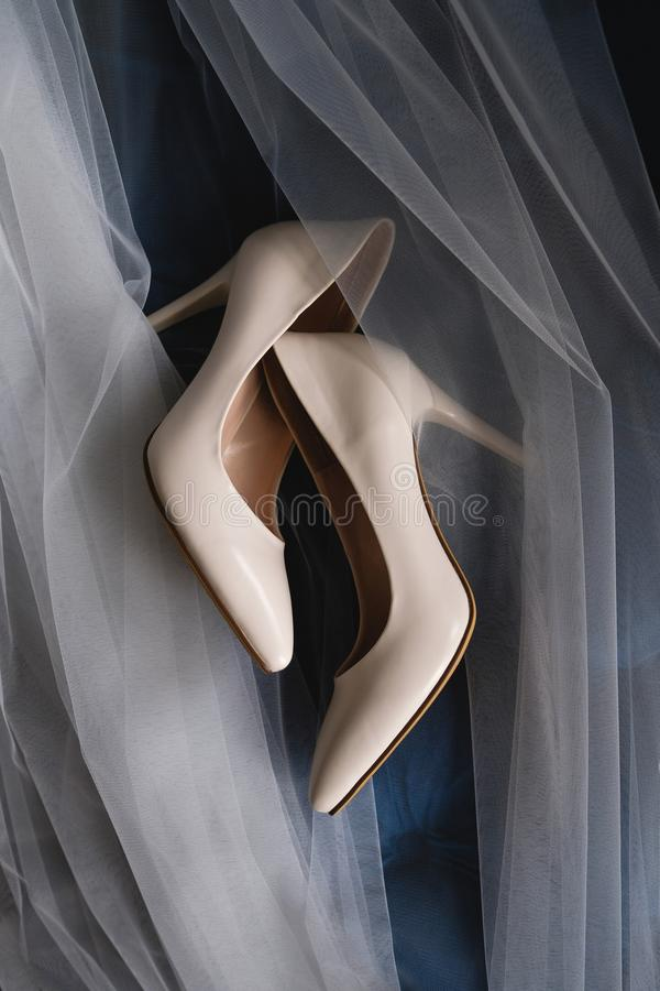Designer wedding beige bride shoes on an expensive velour sofa, tulle or veil. Women`s new modern fashion high-heeled shoes, royalty free stock photos