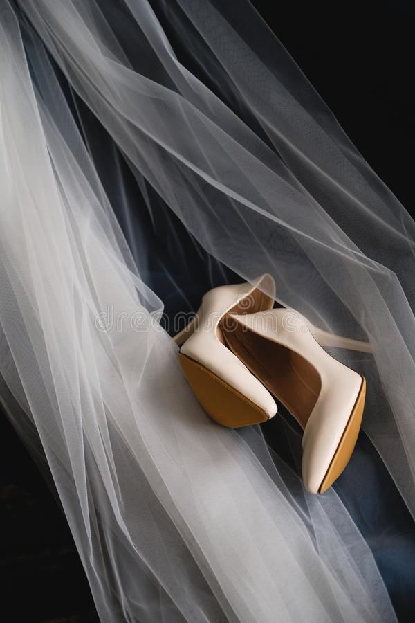 Designer wedding beige bride shoes on an expensive velour sofa, tulle or veil. Women`s new modern fashion high-heeled shoes, stock images