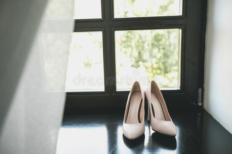 Designer wedding beige bride shoes on the windowsill. Women`s new luxury modern fashion high-heeled shoes made of genuine leather royalty free stock photos