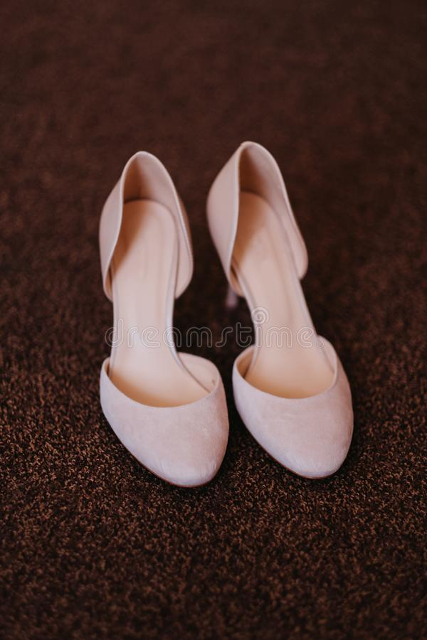Designer wedding white shoes of the bride on a brown carpet. royalty free stock images