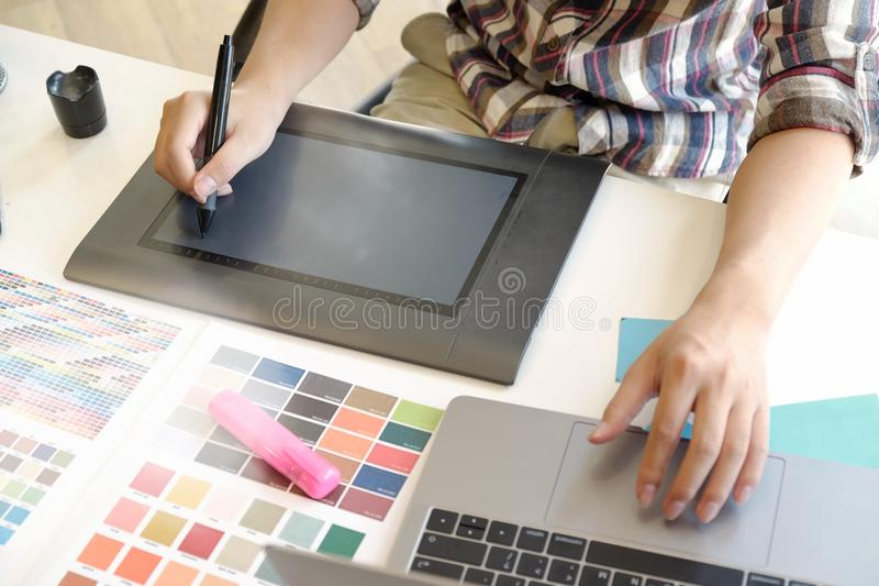Graphic designer using digital tablet and computer in office. Designer working with digital tablet and laptop computer at desk royalty free stock photo