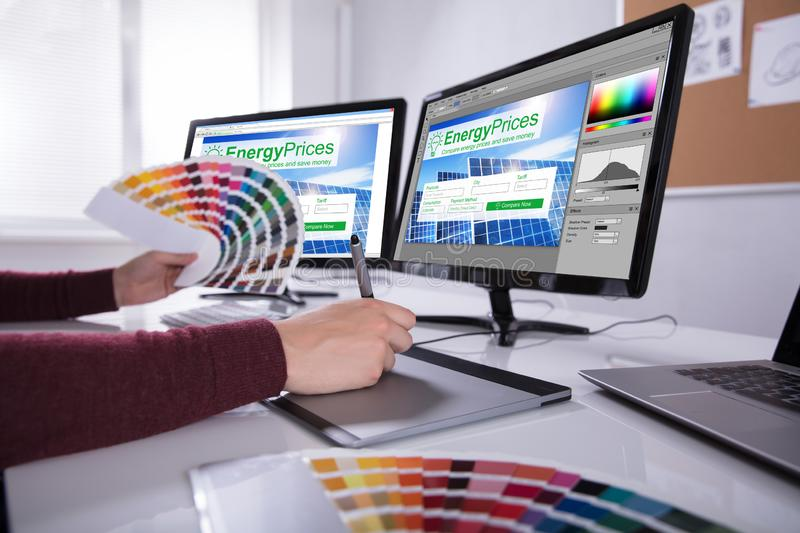 Designer Working On Multiple Computer Screens stock image