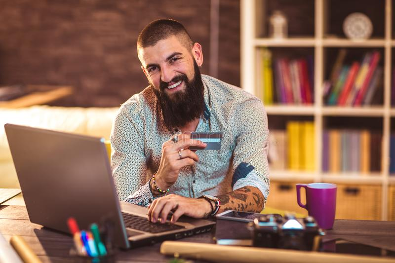 Designer working in office using credit card for online payment royalty free stock photos