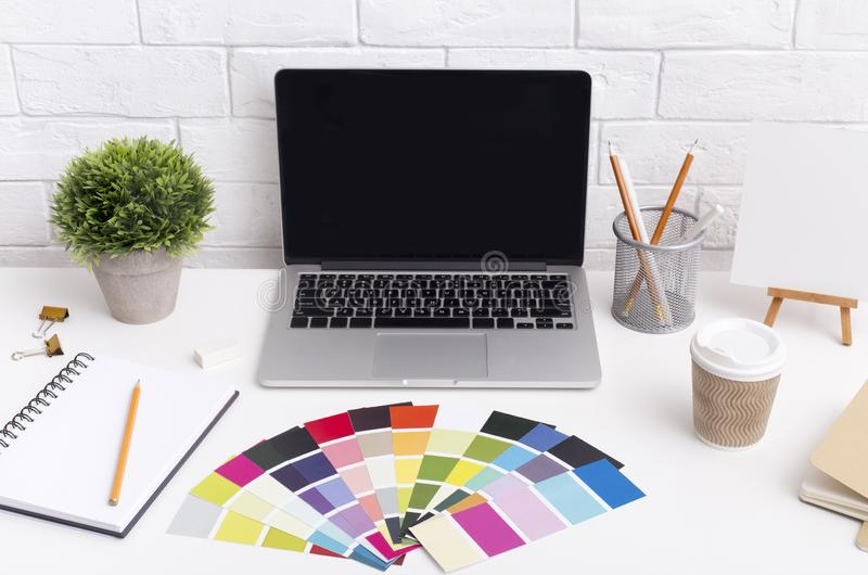 Designer workplace with laptop, cup of coffee and office supplies stock image