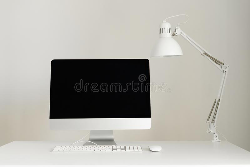 Designer workspace on grey background. Minimalistic home office. Copy space. Keyboard, mouse, computer display with black blank. Screen. Front view stock images