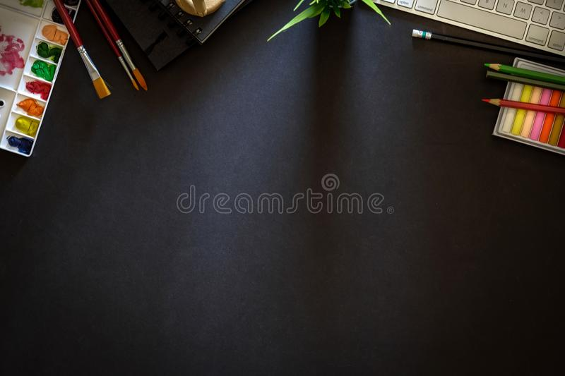 Conceptual image of Artist graphic designer workplace dark surface table. Designer workspace top view with essential elements on dark wooden board royalty free stock images