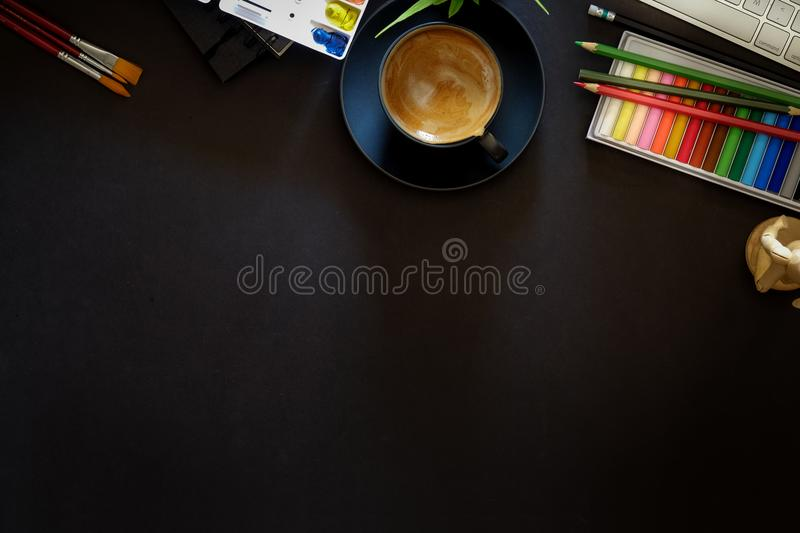 Conceptual image of Artist graphic designer workplace dark surface table. Designer workspace top view with essential elements on dark wooden board royalty free stock photo