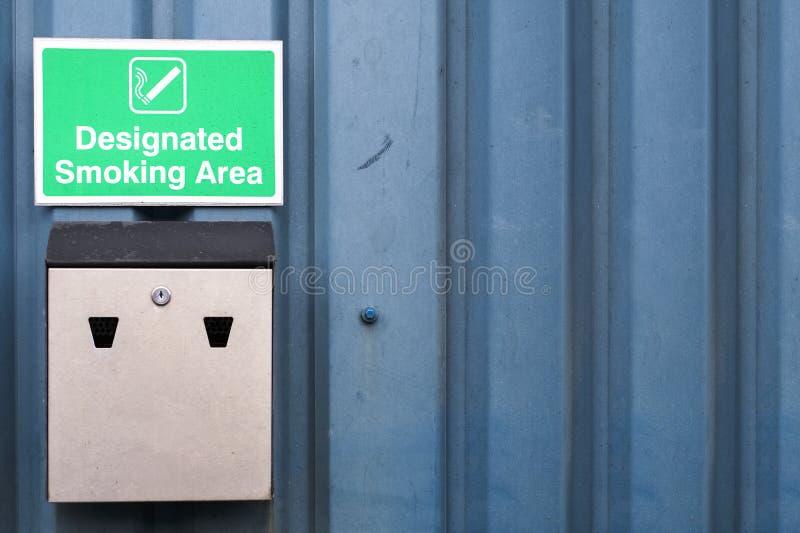 Designerat röka områdestecknet och metallaskamagasinet på arbetsaffärsväggen arkivbild
