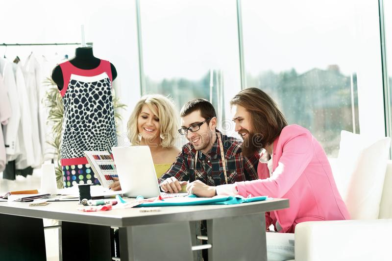 Designergruppenarbeiten über einen Laptop in einem kreativen Büro stockbild