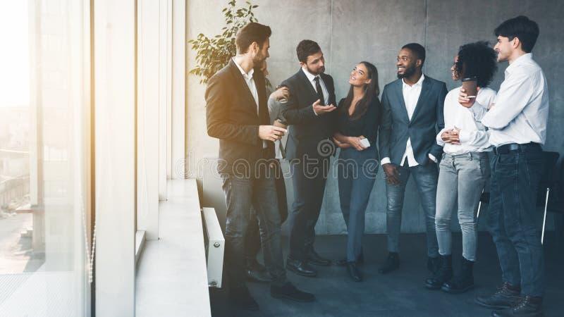 Designers having coffee break near window in office royalty free stock images