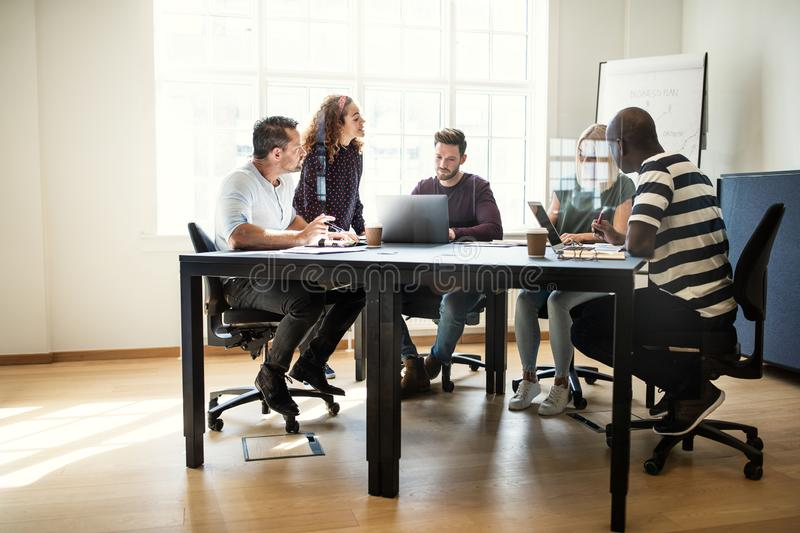 Designers having a meeting together around an office table stock photography
