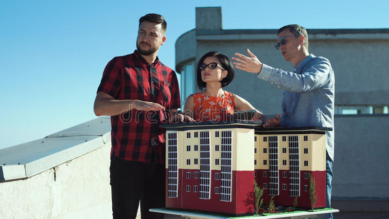 Designers at house model. Group of designers and architects standing at house miniature model and coworking together stock images
