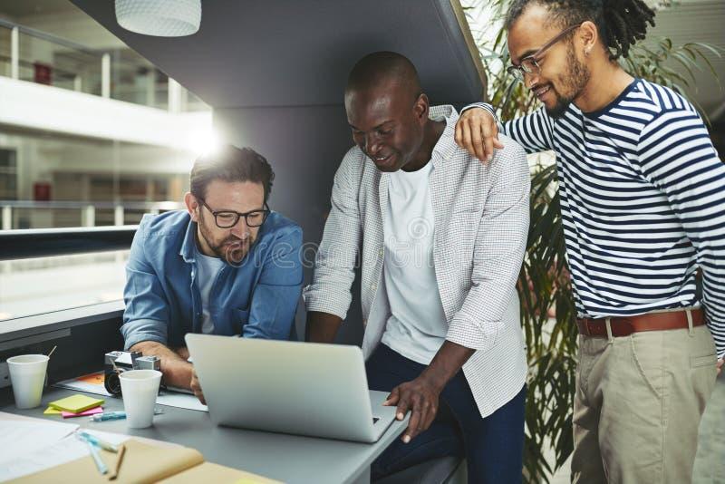 Designers sorridentes usando um laptop em um pod de reunião de escritório fotografia de stock