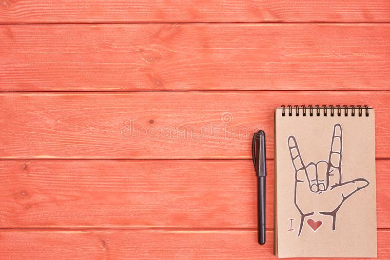 A notebook of Kraft paper with a painted symbol ASL American Sign Language ILY I Love you with black marker which lie on the royalty free stock photography
