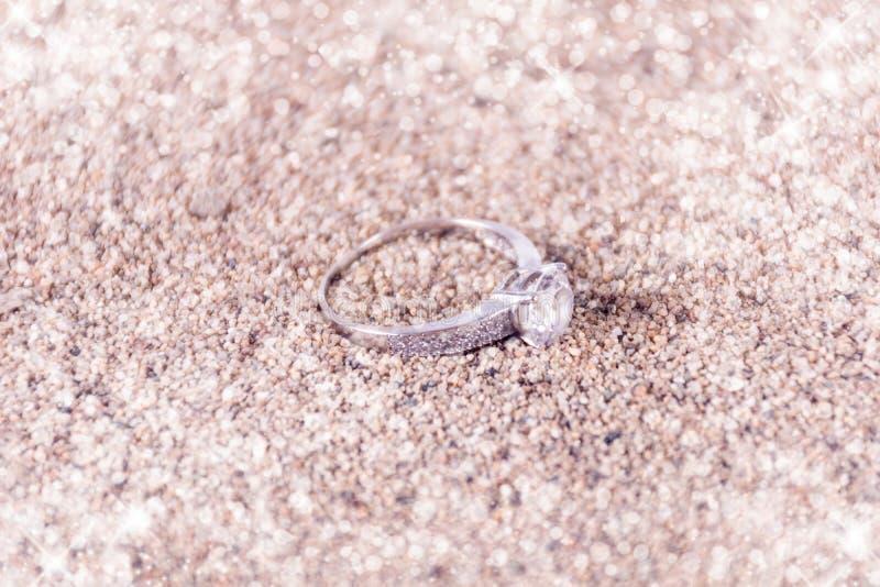 Designersilberhochzeitringe auf Sand und weichem und unscharfem Hintergrund des funkelnden Funkelns stockfotos