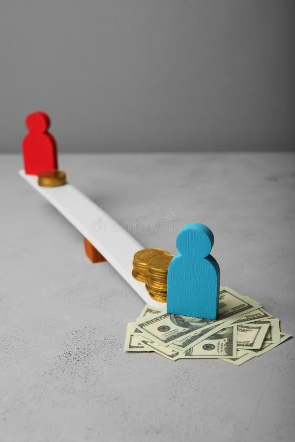 Desigualdade do g?nero no n?vel de conceito do pagamento Moedas em escalas e em figuras dos povos fotos de stock
