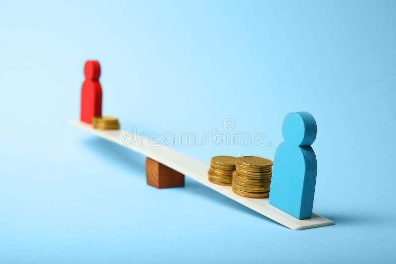 Desigualdade do g?nero no n?vel de conceito do pagamento Moedas em escalas e em figuras dos povos fotos de stock royalty free