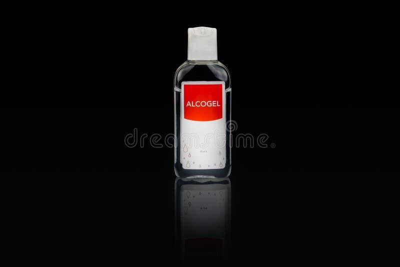 Desinfectante aislado de la mano del alcogel en una pequeña botella plástica con la etiqueta roja imagen de archivo libre de regalías