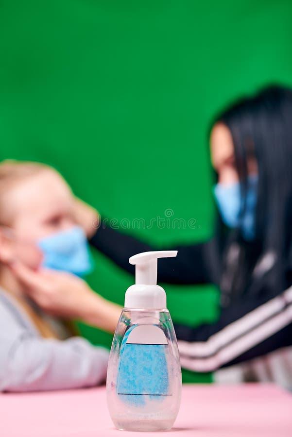 Desinfecterend middel vecht bacteriën Moeder die een blauw medisch masker draagt, kleedt het masker aan op haar baby roze tabel v stock foto's